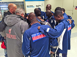 Haiti amputee soccer team prays after arriving at DFW.