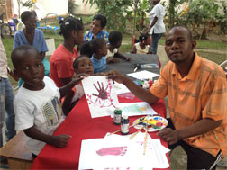 Amputee football player Francillon Chery teachs art to children.